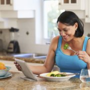 Overweight woman eating healthy while looking at social media on tablet
