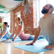 group of people doing yoga in studio