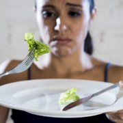 woman eating lettuce on white plate