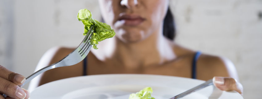 woman eating lettuce on white plate