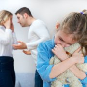 young girl upset with parents fighting in background