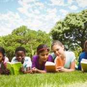 Children reading books on grass at park