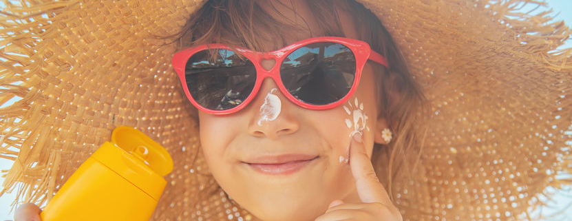 child applying sunscreen on face wearing sunglasses and hat