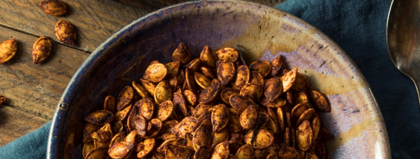 Spicy roasted pumpkin seeds in bowl on table