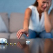 Woman on couch crying with pills on table