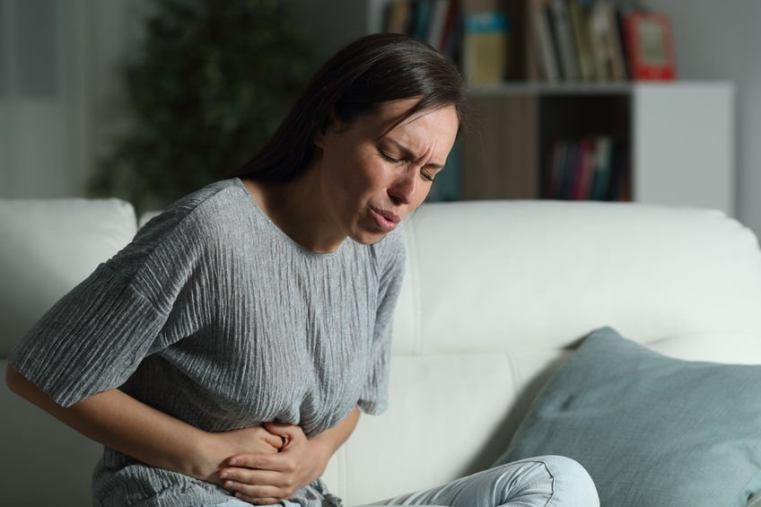 Woman at home suffering belly ache in the night